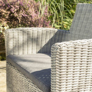 Close up of Palma dining chair- whitewash. Pictured outdoors in the sunshine