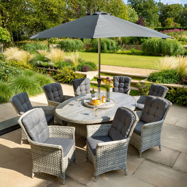 2021 Hartman Heritage 8 Seat Elliptical Dining Set with Lazy Susan and 3 Metre Parasol On A Patio Next to a lawn