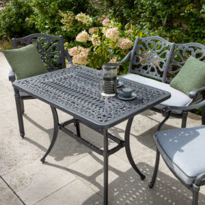 Hartman capri 4 seat coffee set antique grey on patio in front of flower bed