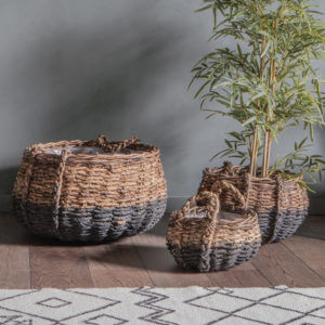 Round woven baskets with plant placed in one sat on wood flooring with patterned rug