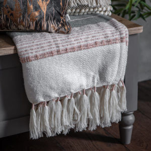 Tassel textured Throw Blush Pink/Grey hanging over table edge with other cushions on top