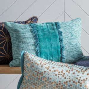 Textured Teal Cotton Cushion with other blue cushions against grey panels