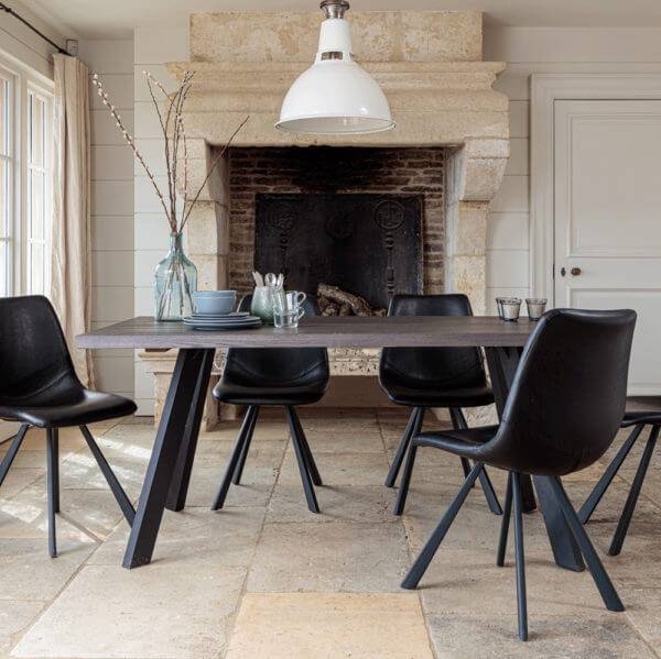Valencia Smokey Dark Oak Dining Set With 5 X Dali Black Leather Dining Chairs in front of large stone fireplace
