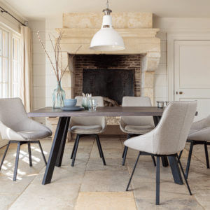 Valencia Smokey Oak Dining Set With 5 X Gaudi Light Grey Dining Chairs in front of large stone fireplace
