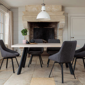 Valencia Light Oak Dining Set With 5 X Gaudi Dark Grey Dining Chairs in front of large stone fireplace