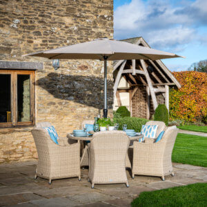 2021 Bramblecrest Monterey 6 Seater Dining Table Set With Parasol On Paved Patio In front Of A Country House